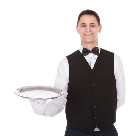 Portrait of confident waiter holding empty tray over white background photo