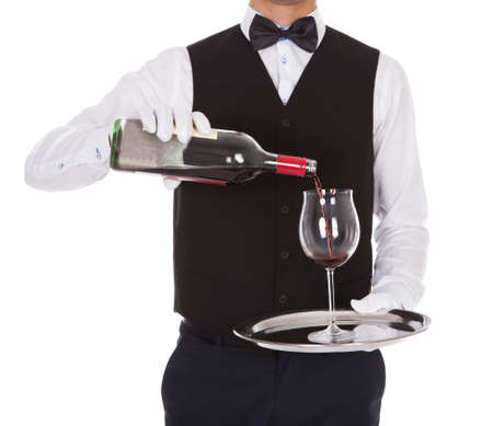 Midsection of male waiter serving red wine in glass against white background photo