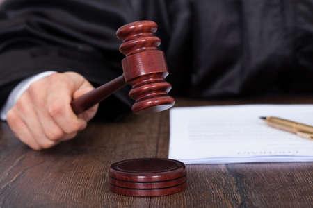 martillo juez: Imagen recortada del juez de dar veredicto por golpear martillo en el escritorio