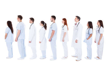 Large diverse group of medical staff in white uniforms with stethoscopes around their necks standing in a queue in profile one behind the other across the frame  isolated on white photo