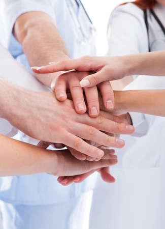 alzando la mano: Los m�dicos y enfermeras en un equipo m�dico de apilamiento manos en una demostraci�n de la cooperaci�n y la solidaridad aislado en blanco Foto de archivo