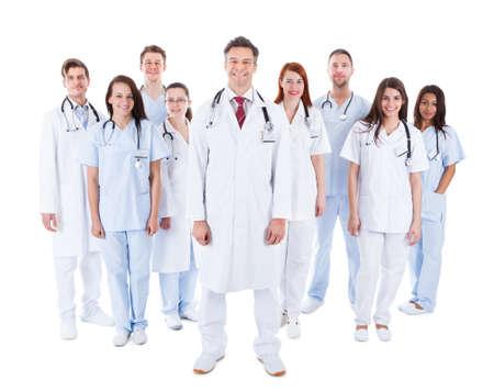 흰색 유니폼 의료진의 큰 다양한 그룹 흰색에 고립 된 잘 생긴 중간 세 수염 의사 또는 의사 뒤에 그룹화 서