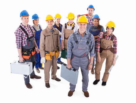 ハンサムな笑みを浮かべて職長高角白で隔離されるによる大規模なツールと hardhats と共にグループ化された立っている多様な職人のチーム鉛します