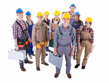 alba�il: Gran equipo de diversos artesanos de pie agrupan junto con sus herramientas y cascos conducir a un amable �ngulo alto capataz guapo aislados en blanco