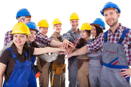 Diverse group of construction workers stacking hands. Isolated on white photo
