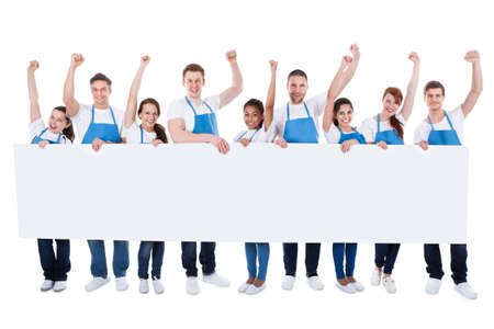 Large diverse multiethnic group of cleaners wearing aprons cheering as they hold a long blank white banner with copyspace for your text or advertisement  isolated on white