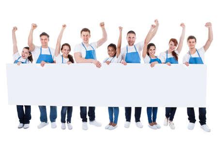 profesionálové: Rozmanitých multietnické skupina čističů nosí zástěry povzbuzování a držet dlouho prázdný bílý nápis s copyspace pro váš text nebo reklamu na bílém
