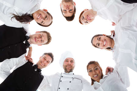 Waiters and waitresses standing in circle. Isolated on white photo