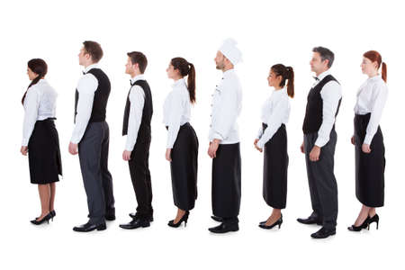 sirvientes: Los camareros y camareras de pie en la cola. Aislados en blanco Foto de archivo