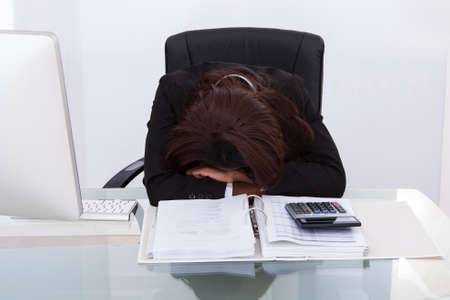 Young businesswoman tired of calculating tax at desk in office photo