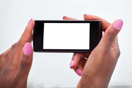 Cropped image of businesswomans hands holding mobile phone in office photo