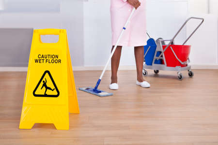 African American female housekeeper cleaning floor in hotel Stock Photo