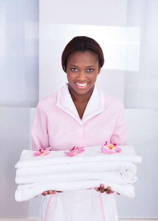 orden y limpieza: Sonriendo ama de casa mujer joven que lleva las toallas en el hotel Foto de archivo