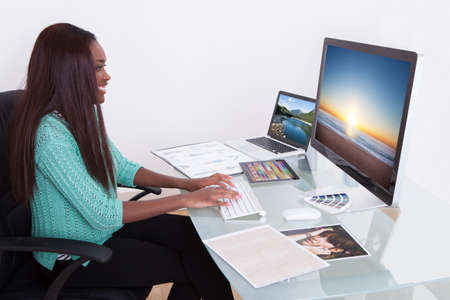 Young female editor using digital tablet at photo agency photo