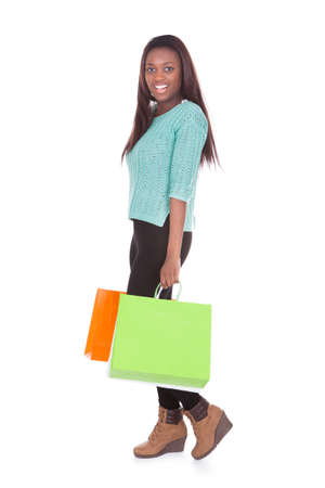 Full length portrait of African American woman carrying shopping bags against white background Stock Photo - 27394148