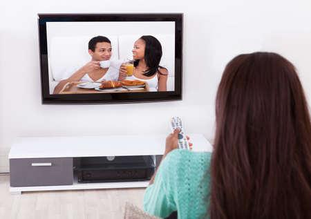 Vista lateral de la joven mujer viendo la televisión en la sala de estar