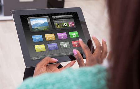 Cropped image African American woman using digital tablet at home photo
