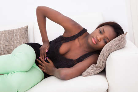 Young African American woman suffering from stomachache lying on sofa at home photo