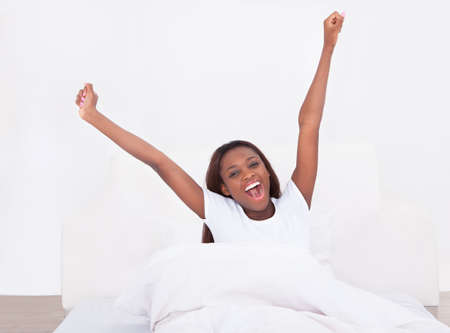 morning routine: Portrait of young African American woman stretching in bed at home