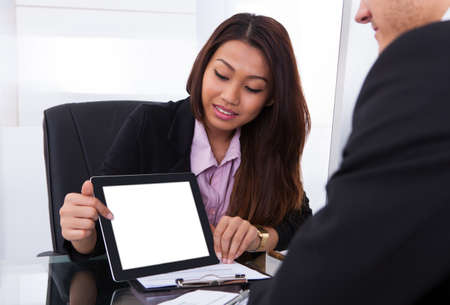 Businesswoman showing digital tablet to male colleague at desk in office photo