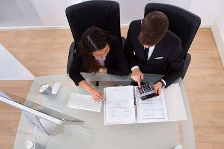 Business colleagues calculating tax together at desk in office photo