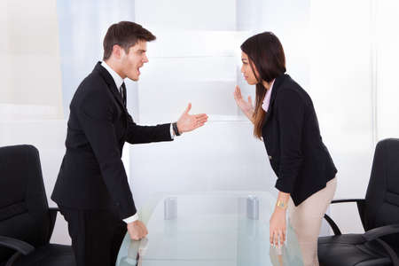 Side view of business people quarreling at desk in office photo
