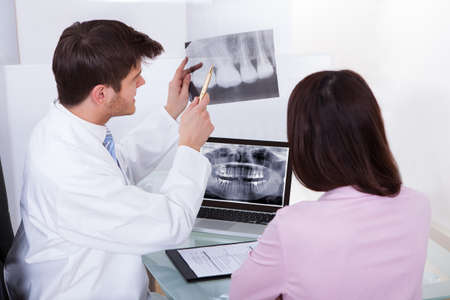 Male dentist explaining dental Xray to female patient in clinic photo