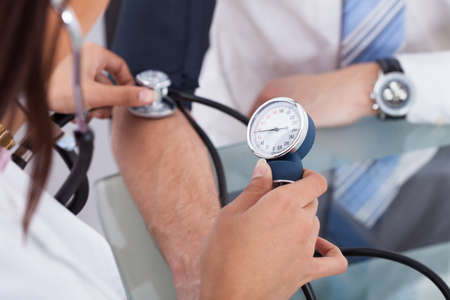 doctor office: Cropped image of female doctor checking businessmans blood pressure in clinic Stock Photo