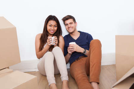 Portrait of young multiethnic couple holding coffee mugs while sitting on floor in new home photo