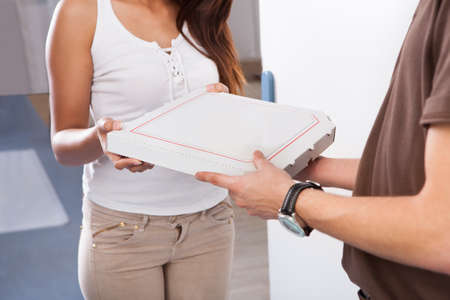 pizza delivery: Smiling young woman receiving pizza from delivery man at home Stock Photo