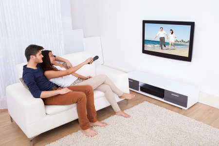 sit: Young couple watching TV while sitting on sofa in living room at home