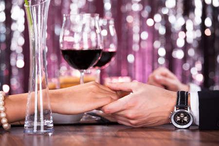 diner romantique: Couple romantique tenant la main de l'autre à dîner dans un restaurant