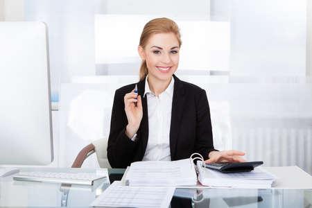 auditor�a: Retrato De negocios joven feliz sentado en el escritorio C�lculo Finanzas