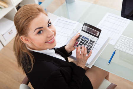financial audit: Portrait Of Happy Young Businesswoman Sitting At Desk Calculating Finance