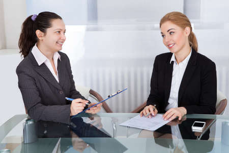 Portrait Of Two Happy Businesswoman Discussing In Office photo
