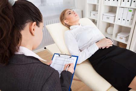 terapia psicologica: Psiquiatra Mujer joven que sostienen el sujetapapeles Empresaria Examinar