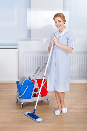 Portrait Of Smiling Young Female Maid Holding Mop photo