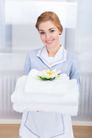 hotel staff: Portrait Of Happy Young Maid Holding Towels