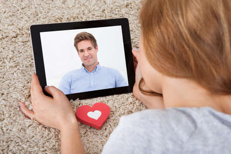 Close-up Of Young Woman Having Video Chat On Digital Tablet photo