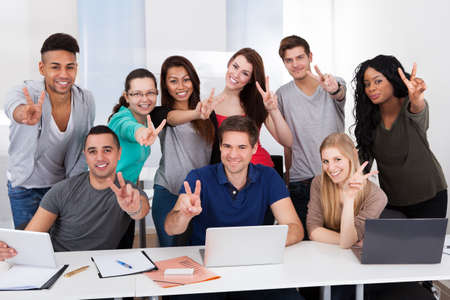 Group portrait of multiethnic college students gesturing victory sign together in classroom photo