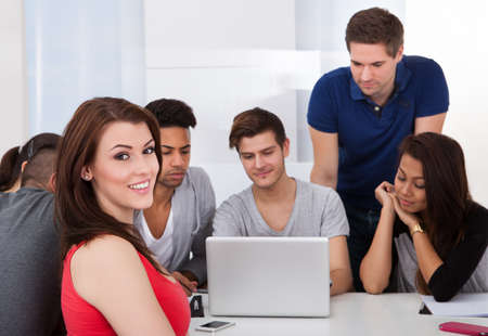Portrait of beautiful university student sitting with classmates using laptop in classroom photo