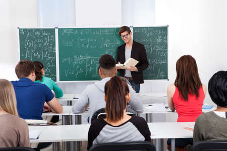Young teacher teaching mathematics to university students in classroom photo