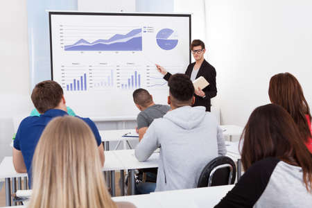teach: Young teacher teaching graphs drawn on whiteboard to college students in classroom