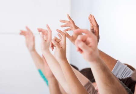 Fila de los estudiantes universitarios multiétnicas que levantan las manos en el aula