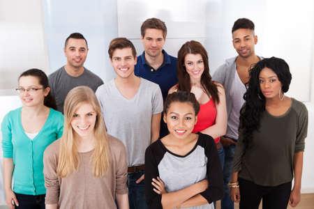 graduacion de universidad: Retrato de grupo de estudiantes sonrientes universitarios multiétnicas de pie juntos en el aula