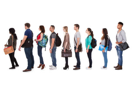 Full length side view of multiethnic college students standing in a row against white background photo