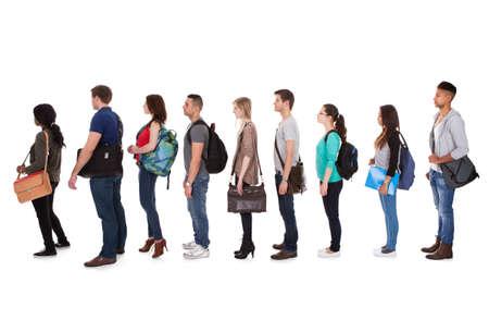 file d attente: Pleine vue de côté de longueur d'étudiants multiethniques debout dans une rangée sur fond blanc