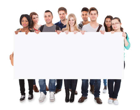 Full length portrait of confident multiethnic college students displaying blank billboard against white background photo