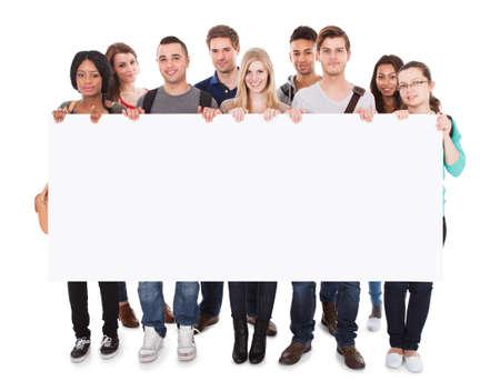 vysoká škola: Po celé délce portrét jistý multietnických vysokoškoláků zobrazování prázdný billboard proti bílému pozadí Reklamní fotografie