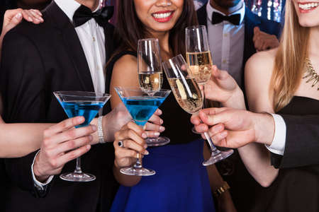 Cropped image of young friends toasting drinks at nightclub photo